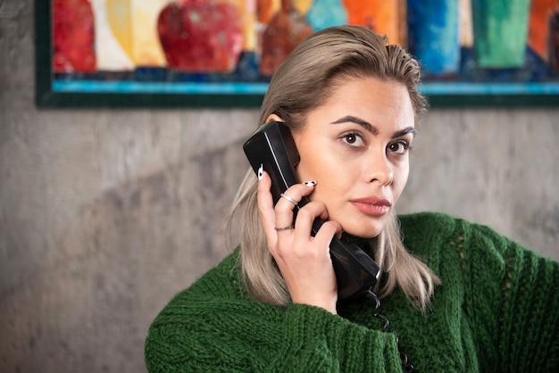 Foto der jungen frau, die ein schwarzes telefon hält