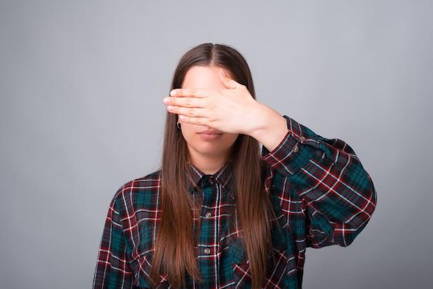 Foto der jungen frau, die ihr gesicht mit handfläche bedeckt