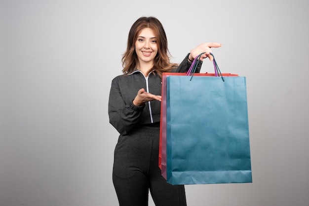 Foto der jungen frau mit einkaufstüten und winkender hand.