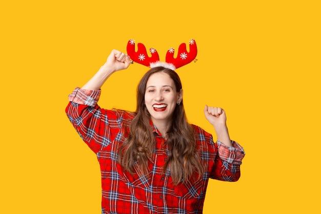Foto der jungen fröhlichen frau, die winterferien über gelbem hintergrund feiert