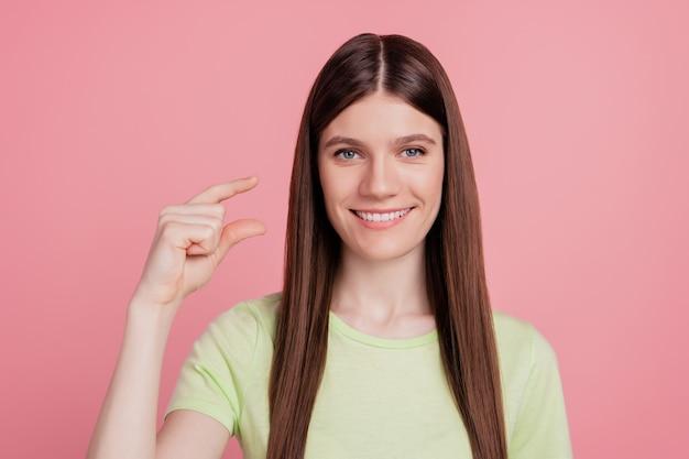 Foto der jungen fröhlichen frau glückliches lächeln zeigen finger kleine kleine winzige größe isoliert über rosafarbenem hintergrund