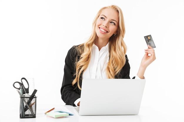 Foto der jungen geschäftsfrau, die am tisch sitzt und kreditkarte beim arbeiten am laptop, lokalisiert hält