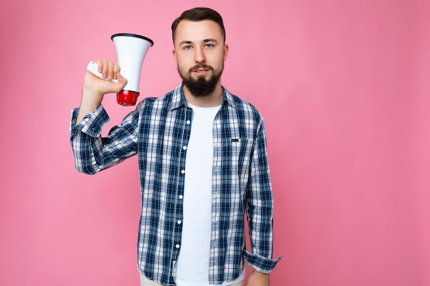 Foto der jungen gutaussehenden ernsthaften brünetten männlichen person mit bart mit aufrichtigen gefühlen, die t-shirt und stilvolles karohemd tragen, lokalisiert über rosa und halten megaphon.