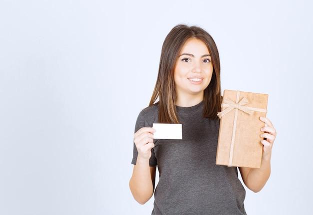 Foto der jungen lächelnden frau, die eine geschenkbox mit karte hält.