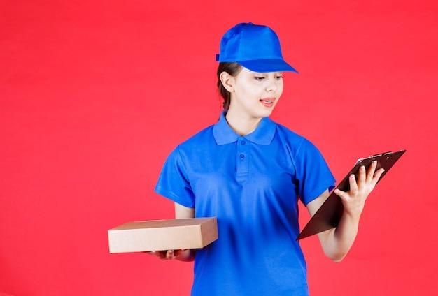 Foto der jungen lieferfrau, die kartonkasten hält und klemmbrett betrachtet.