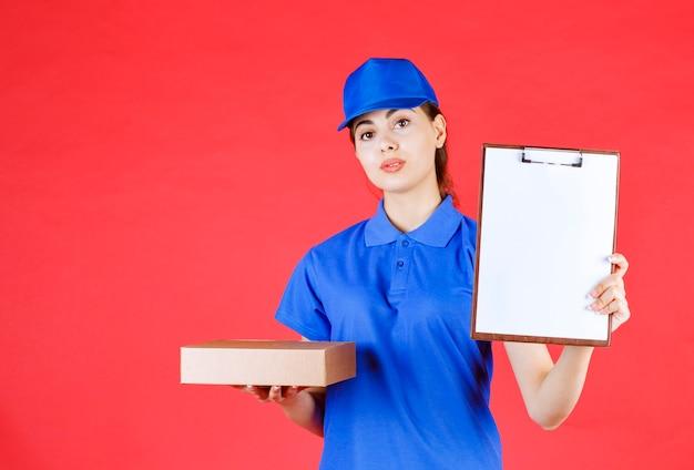 Foto der jungen lieferfrau, die kartonkasten und klemmbrett auf rot hält.