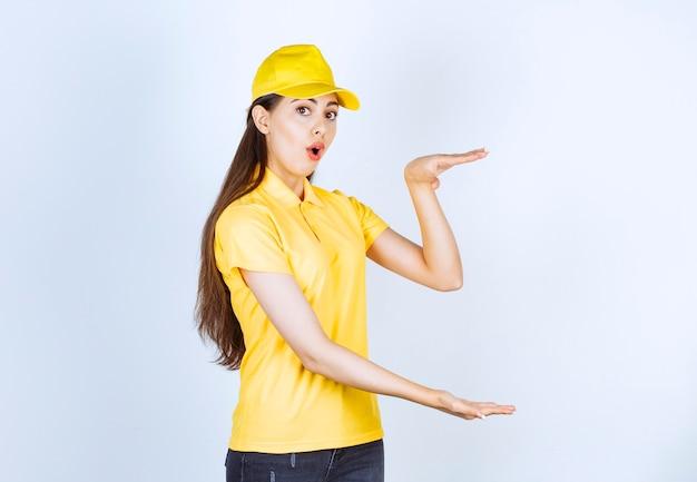 Foto der jungen lieferfrau, die offenen raum über weißer wand hält.