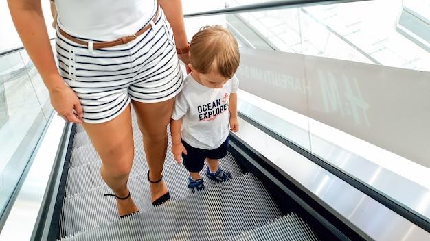 Foto der jungen mutter, die ihren kleinen sohn mit der hand hält, während sie auf der rolltreppe im einkaufszentrum fährt?