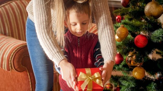 Foto der jungen mutter, die zu weihnachten überrascht und ihrem kleinen sohn neben dem weihnachtsbaum im wohnzimmer eine geschenkbox gibt