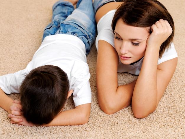 Foto der jungen mutter und ihres ungehorsamen schuldigen weinenden sohnes, der auf dem boden liegt
