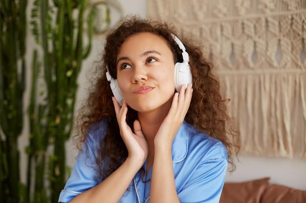 Foto der jungen netten denkenden afroamerikanischen lockigen frau hält kopfhörer, hört lieblingsmusik in kopfhörern, schaut nachdenklich weg.