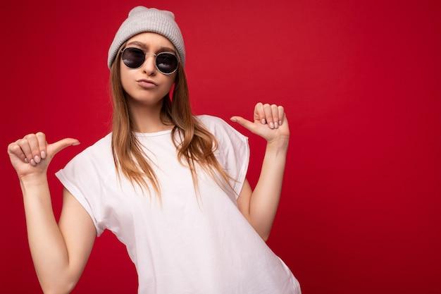 Foto der jungen positiven coolen attraktiven dunkelblonden frau mit aufrichtigen gefühlen, die lässiges weiß tragen