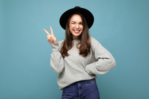 Foto der jungen positiven glücklich lächelnden schönen frau mit aufrichtigen gefühlen, die stilvolle kleidung einzeln über dem hintergrund mit kopienraum trägt und friedensgeste zeigt.