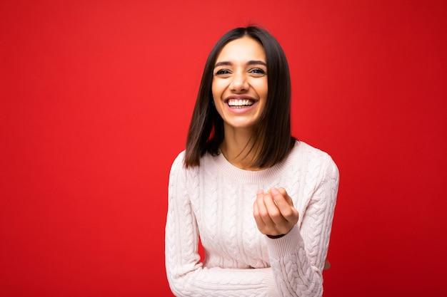 Foto der jungen positiven glücklich lächelnden schönen frau mit aufrichtigen gefühlen, die stilvolle kleidung einzeln über dem hintergrund mit kopienraum trägt.