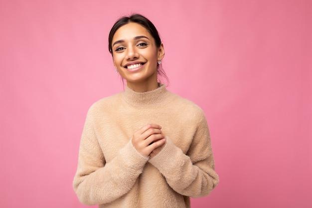 Foto der jungen positiven glücklich lächelnden schönen frau mit aufrichtigen gefühlen, die stilvolle kleidung trägt, die über dem hintergrund mit kopienraum lokalisiert wird.