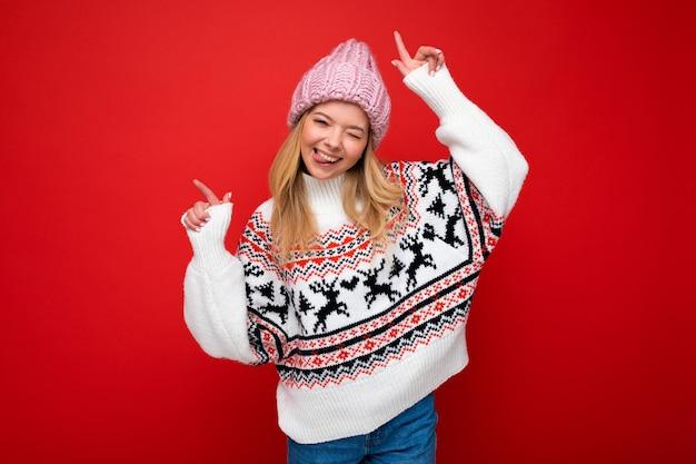 Foto der jungen positiven glücklichen attraktiven blonden frau mit aufrichtigen gefühlen, die rosa strickmütze trägt