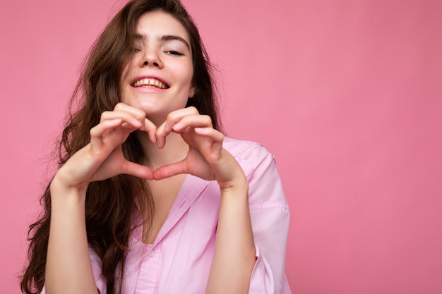Foto der jungen positiven glücklichen lächelnden schönen wellenförmigen brünetten frau mit aufrichtigen gefühlen