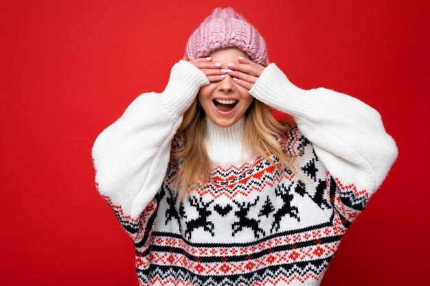 Foto der jungen positiven glücklichen schönen blonden dame mit aufrichtigen emotionen, die rosa strickmütze und winterpullover einzeln auf rotem hintergrund mit leerem raum trägt und die augen mit den händen bedeckt.