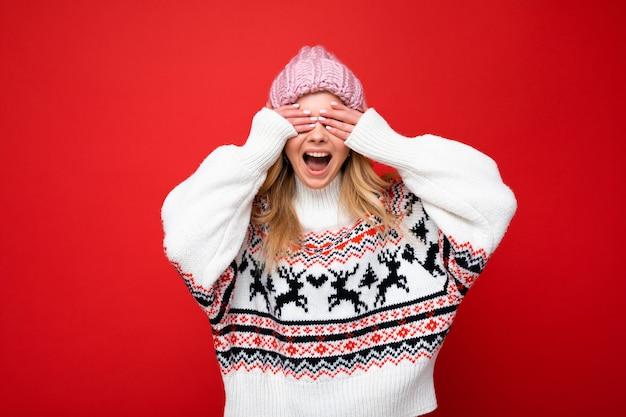 Foto der jungen positiven glücklichen schönen blonden dame mit aufrichtigen gefühlen, die rosa strickmütze trägt