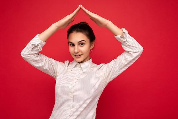 Foto der jungen positiven glücklichen schönen brünetten frau mit aufrichtigen gefühlen, die weißes hemd trägt