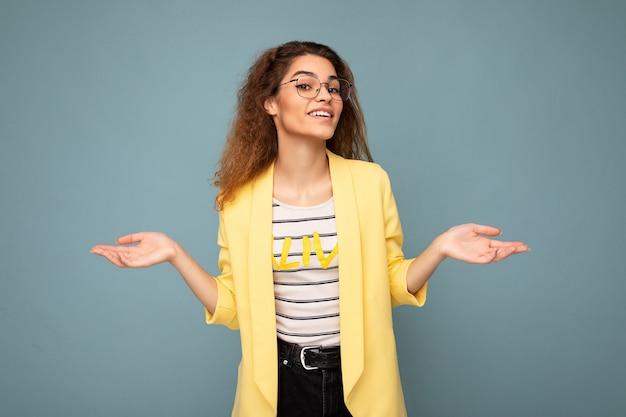 Foto der jungen positiven nachdenklichen schönen brünetten lockigen frau mit aufrichtigen gefühlen, die tragen