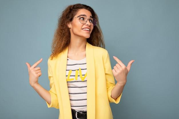 Foto der jungen, positiven, schönen, brünetten, lockigen frau mit aufrichtigen emotionen, die lässiges gelb trägt