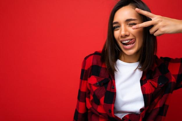 Foto der jungen positiven sexy glücklichen lächelnden schönen frau mit aufrichtigen gefühlen, die stilvolle kleidung tragen