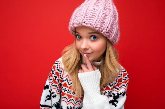 Foto der jungen schönen blonden dame mit aufrichtigen gefühlen, die rosa strickmütze und winter trägt