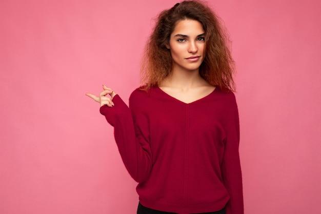 Foto der jungen schönen brünetten gewellten frau mit aufrichtigen emotionen, die lässiges rosa trikot trägt