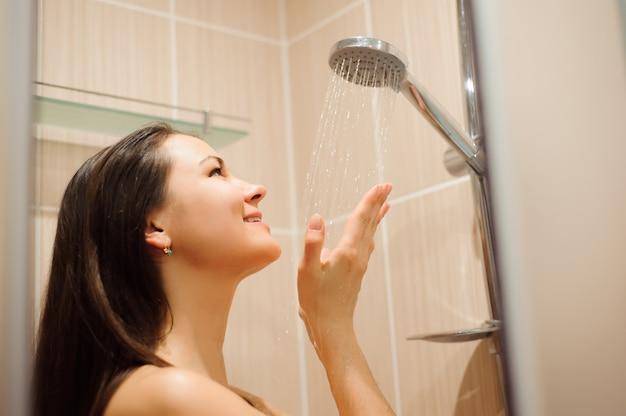 Foto der jungen schönen frau, die entspannende dusche nimmt