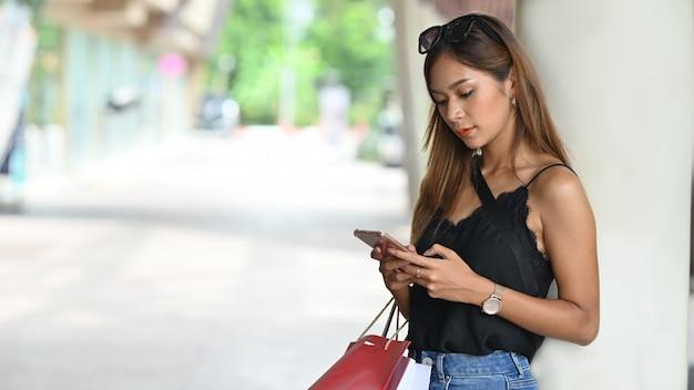 Foto der jungen schönen frau im schwarzen unterhemd unter verwendung des smartphones beim stehen mit dem tragen einer einkaufstasche nach beendetem einkauf am städtischen einkaufszentrum mit unscharfer straße