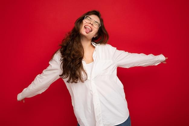 Foto der jungen schönen glücklichen brünetten frau mit weißem hemd und optischer brille sexy sorglos