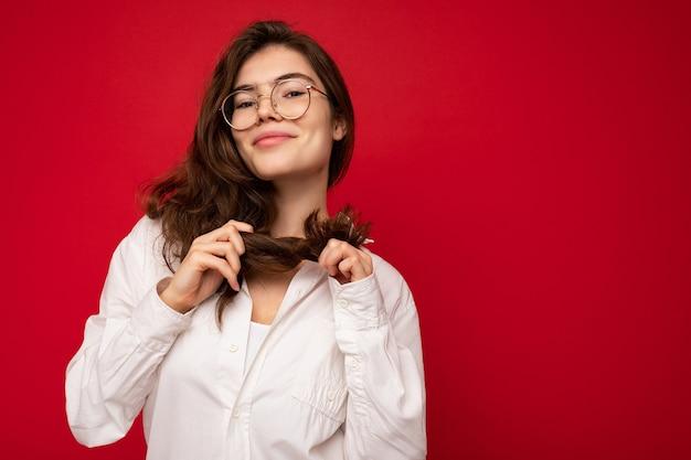 Foto der jungen schönen glücklichen lächelnden brünetten frau mit weißem hemd und optischer brille sexy