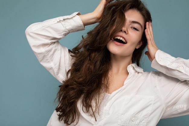 Foto der jungen schönen glücklichen lächelnden gelockten brunettefrau, die weißes hemd sexy unbeschwerte frau trägt