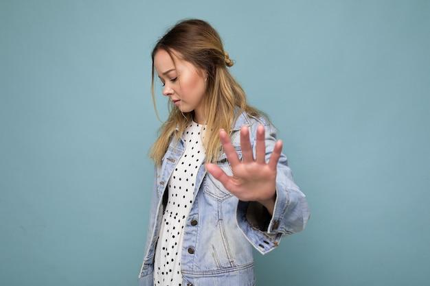 Foto der jungen traurigen verärgerten attraktiven blonden frau mit aufrichtigen gefühlen, die blaue jeansjacke trägt