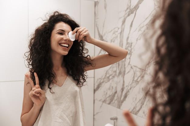 Foto der kaukasischen lächelnden frau mit dem langen dunklen haar, das im spiegel schaut, während auge mit wattepad im badezimmer bedeckt