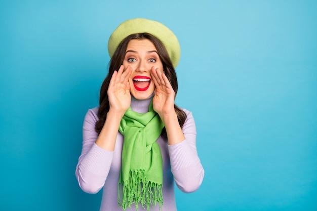 Foto der kühlen reisenden dame halten hände nahe mund schreien informationen verkauf einkaufen tragen grüne baskenmütze hut lila rollkragenpullover schal isoliert blaue farbe wand