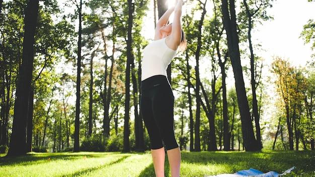Foto der lächelnden frau mittleren alters, die yoga asana praktiziert. persong, die in der natur meditiert. balance und harmonie von körper und geist