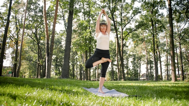Foto der lächelnden glücklichen frau 40 jahre alt, die yogaübungen auf fitnessmatte im wald macht. harmonie des menschen in der natur. menschen mittleren alters, die sich um die geistige und körperliche gesundheit kümmern Premium Fotos