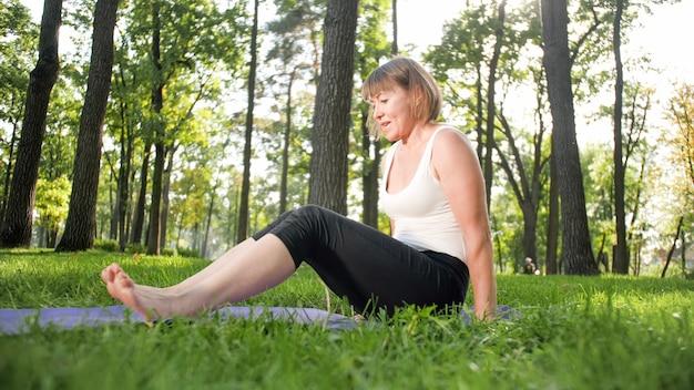 Foto der lächelnden glücklichen frau 40 jahre alt, die yogaübungen auf fitnessmatte im wald macht. harmonie des menschen in der natur. menschen mittleren alters, die sich um die geistige und körperliche gesundheit kümmern