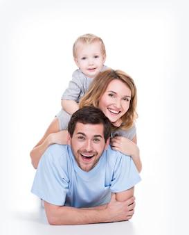 Foto der lächelnden jungen eltern mit dem kleinen kind, das auf dem boden liegt - lokalisiert