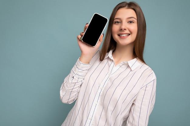 Foto der lächelnden jungen frau, die gut aussehend trägt lässiges stilvolles outfit, das isoliert steht