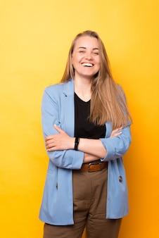 Foto der lächelnden jungen geschäftsfrau, die über gelbem hintergrund steht