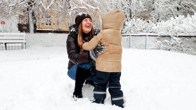 Foto der lächelnden mutter im mantel mit ihrem süßen sohn in beigefarbener jacke viel spaß beim spielen der schneebälle auf dem spielplatz im park
