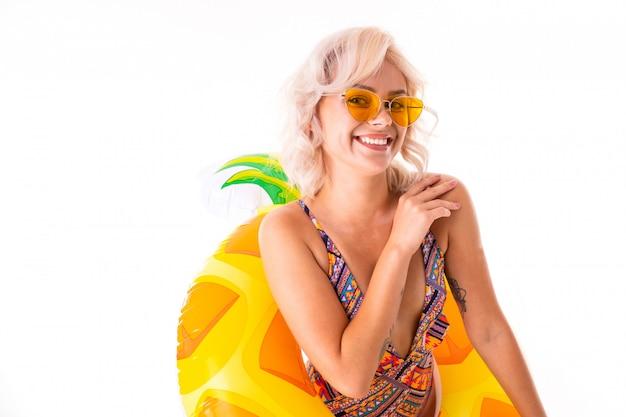 Foto der lächelnden schönen frau, die badeanzug trägt, der im schwimmring lokalisierten weißen hintergrund steht