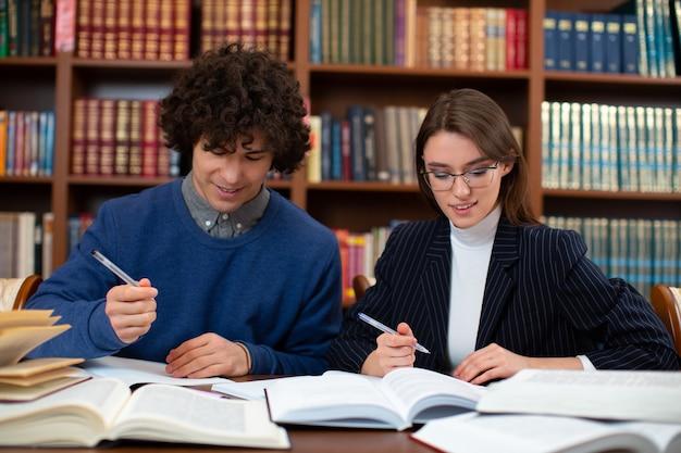 Foto der lernprozess der schüler. ein junger mann und ein mädchen sitzen in der bibliothek