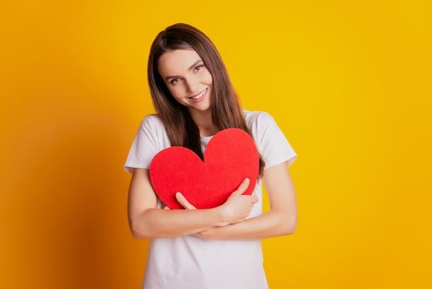 Foto der liebevollen dame, die herzform umarmt, liebt sich selbst konzept trägt weißes t-shirt, das auf gelbem hintergrund posiert