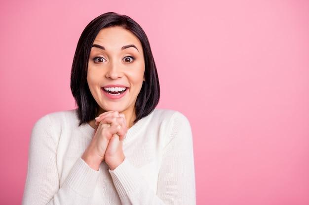 Foto der lustigen brünettenfrau mit weißem pullover lokalisiert auf rosa