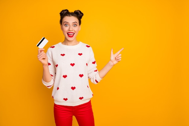 Foto der lustigen dame halten plastikkreditkarte, die finger leeren raum anzeigt, der schöne verkaufspreise empfiehlt, tragen herzmuster weißen pullover