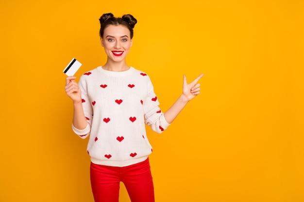 Foto der lustigen dame halten plastikkreditkarte, die online-kauf berät, der fingerleerraum zeigt, trägt herzmuster weißen pullover